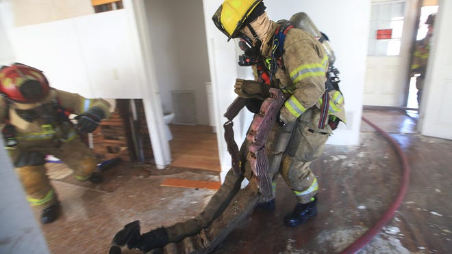Hutchinson Fire Dept. Capt. Gerald Wiens, left, and Firefighter Noah Martin conduct a training exercise where they rescue a training dummy inside of a house Friday afternoon.