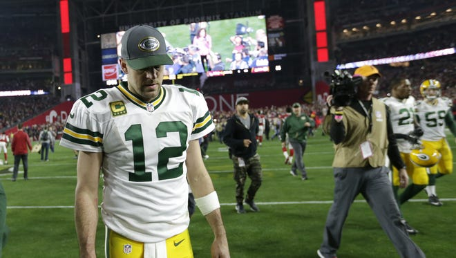 Green Bay Packers quarterback Aaron Rodgers hangs his head as he leaves the field following an overtime loss to the Cardinals.