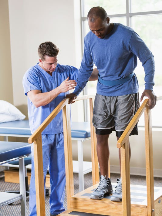 Physical therapist helping patient on stairs