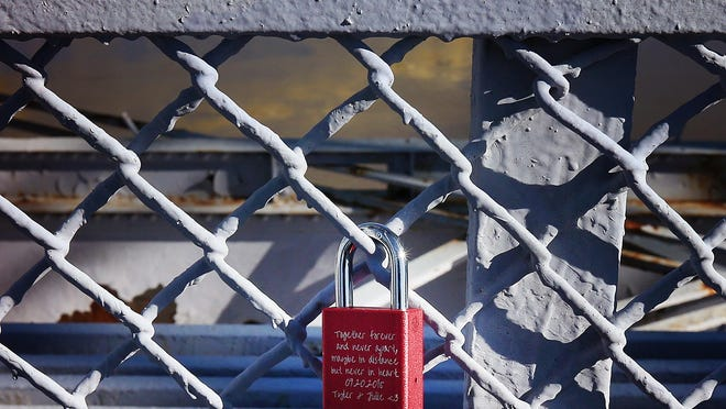 """Padlocks dubbed """"love locks"""" have recently been removed from the Purple People Bridge. Pictured is a lock that remains. Reader Janis Eppensteiner says the locks shouldn't be removed from the bridge because they reinforce the value of the goodness of humanity."""