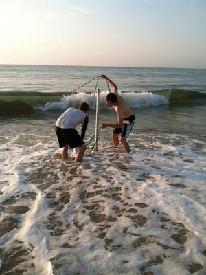 University of Delaware graduate students James Heiss and Thijs Lanckreit mount a pressure sensor to a metal frame in the swash zone along Delaware Bay to measure incoming wave conditions.