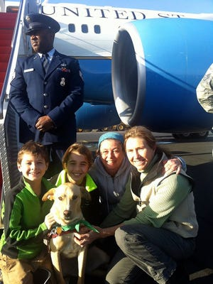 The family of Beau Biden poses for a picture with their new dog Indi, who was left abandoned in Mississippi.