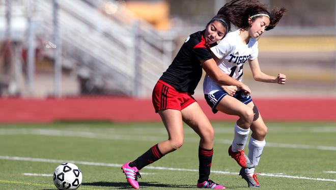 Incarnate Word Academy's Sabrina De Santiago (left) and Carroll's Layla Villarreal fight over the ball in the first half of their game in the Mira's Gulf Coast Classic Soccer tournament at Cabaniss Multipurpose Stadium on Thursday, Jan. 11, 2018. IWA won the game 5-0.