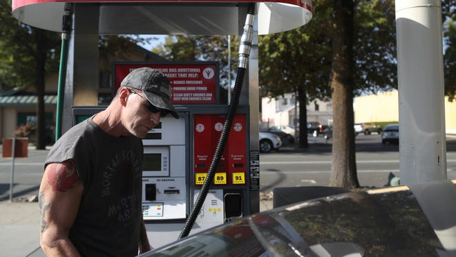 Tim Robbins pumps gas at the FuelGood station on Pine Street in downtown Redding. He paid a higher price for gasoline as a statewide gas went into effect.