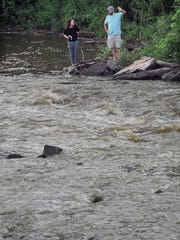 Hattie Johnson, a landscape designer at RiverRestoration.org, looks at the Big Sioux River in Falls Park with Mitchell Joldersma. Joldersma and Johnson spent roughly four hours Tuesday morning touring the river, stopping along the way for on-site analysis.