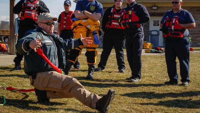 Dave Moore, Dive Rescue International trainer, demonstrates the use of a crab walk to distribute body weight if one were to walk across unsafe ice. Firefighters throughout Ohio came for ice rescue training at Miami Meadows Park Wednesday February 3, 2016.