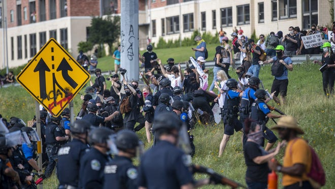 Protesters run as Austin police officers shoot rubber bullets at them near Interstate 35 and Eighth Street in downtown Austin in May. Demonstrators protested over the death of George Floyd, who suffocated at the hands of Minneapolis police.