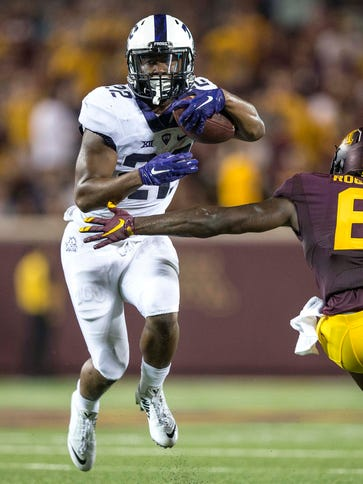 TCU running back Aaron Green (22) tries to evade the