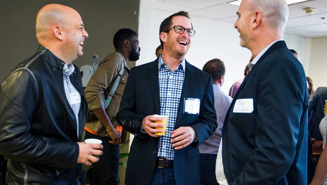 Jonathan Ariano, of Osborn Maledon (left) Greg Head, chief marketing officer for Infusionsoft, and Robert La Loggia, chief executive officer of AppointmentPlus (right) chat before the start of Phoenix Startup Week on the 19th floor of One 11 Tower in downtown Phoenix, Monday, Feb. 23, 2015.