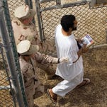 A 2008 photo shows a female guard (foreground) and a male guard escorting a detainee at Camp Delta 4 on the U.S. Military Base in Guantanamo Bay, Cuba.