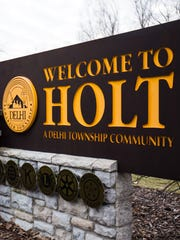 The entrance sign to Holt, Mich., sits off on the side