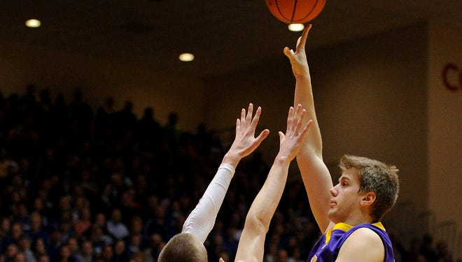 Guerin Catholic forward Aaron Brennan with a hook shot over Greensburg forward Sean Sellers during the Class 3A Semistate game, Saturday, March 22, 2014, inside the Tiernan Center at Richmond High School.