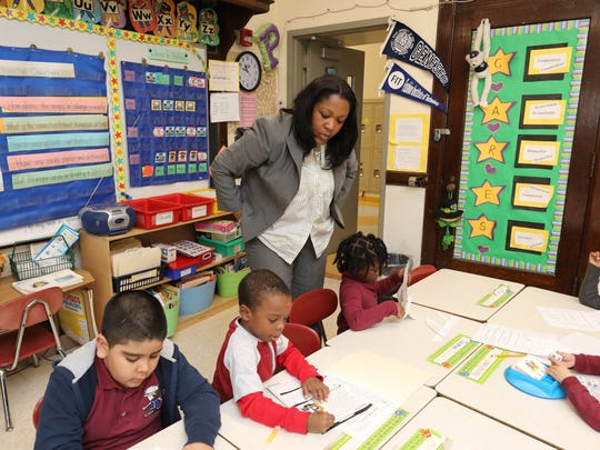 Colleen Crawford, the principal of the Columbus Elementary School on North High Street in Mount Vernon, looks over some students in Lynne Petrone's 1st grade class, Jan. 30, 2018.