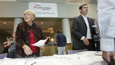 Charlotte Garst and Ed Cegnas, two employees of 21st Century Insurance, work at a job fair at the company's Brandywine Hundred offices on Sept. 29, 2009. The company has announced that positions are being eliminated.