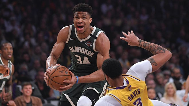 Milwaukee Bucks forward Giannis Antetokounmpo knocks down Los Angeles Lakers forward Anthony Davis as he drives to the basket in a game on March 6.