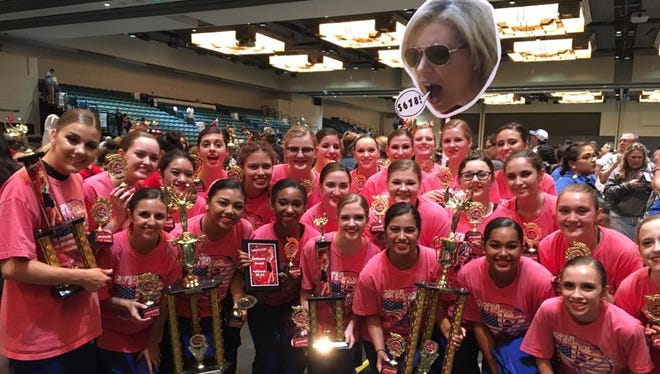 The Cooper Cougarettes dance team celebrates two national titles, in the pom and novelty competitions, and a runner-up performance in contemporary at the national competition in Galveston while holding a cardboard cutout of director Kimberely McMillon.