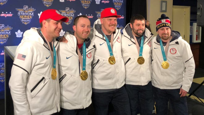 The U.S. men's Olympic curling team poses with their gold medals before the NHL's outdoor game in Annapolis, Md.