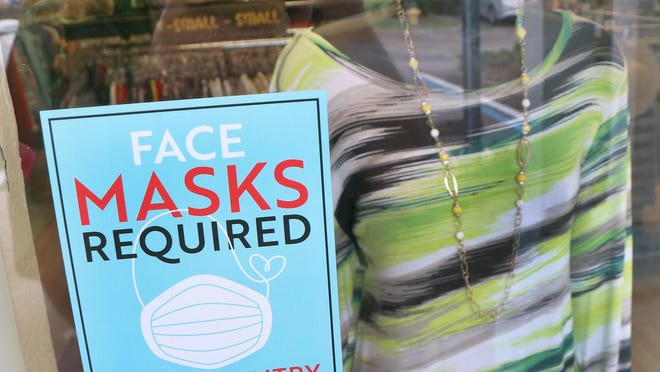 A window sign lets customers know face masks required at the Fashion Safari recently in Port Orange. Some government agencies are instituting stronger face mask requirements than others.