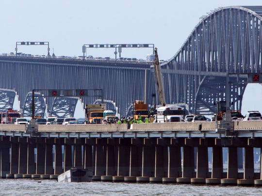 Rescue units use a crane to lift a tractor trailer out of the Chesapeake Bay near Stevensville, Md., after it plunged over the eastbound span of the Bay Bridge on Aug. 10, 2008. the bridge is one of several that are served by a ride-assistant program for those frightened by the bridge.