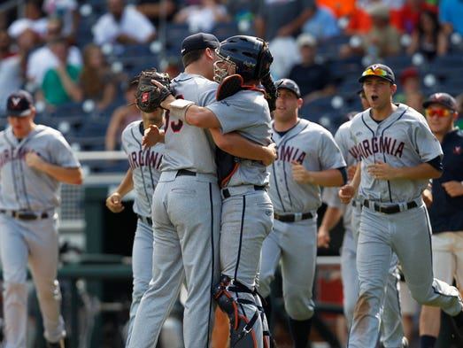 Virginia closer Nick Howard, left, celebrates with catcher Robbie Coman after defeating Mississippi 4-1 to advance to the College World Series finals.
