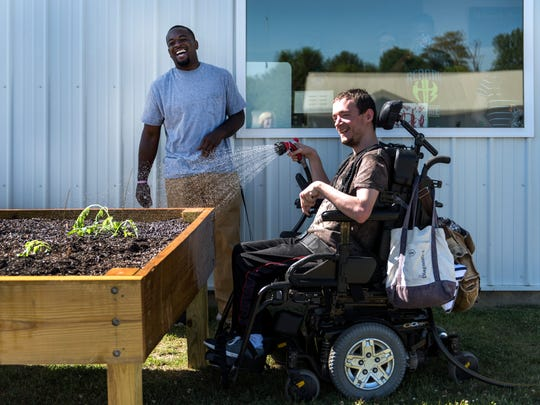 KJ O'Neal, a direct support professional, (left) laughs as he watches Joey Newton (right) water plants in a raised garden bed outside of the Hugh Edward Sandefur Center in Henderson, Kentucky, on Tuesday, June 20, 2017. The new gardening project aims to teach them how to grow and raise crops in hopes to sell them in the future.