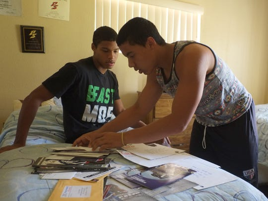 Twins Tayler (left) and Tyler Hawkins sort through an assortment of recruiting letters in their bedroom in Palm Springs. Without a college scholarship, college may not have been a financially viable option.