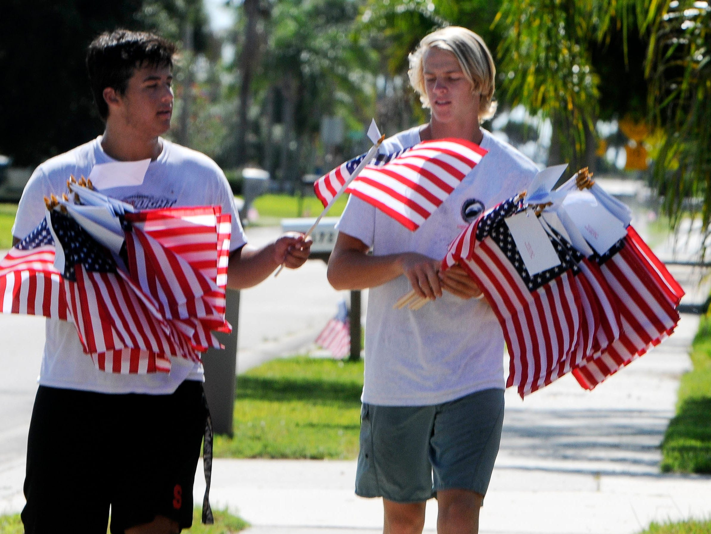Alex Iervasi and Noah Mumme help set out American flags Thursday morning in Satellite Beach. Students from Satellite High's football and ROTC squads help distribute American flags as part of a fundraiser for the school.