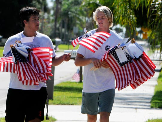 Alex Iervasi and Noah Mumme help set out American flags