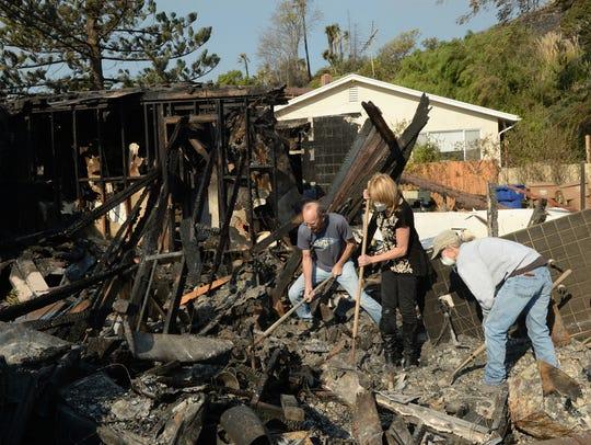 Ventura homeowner Adele Bonge, center, is assisted