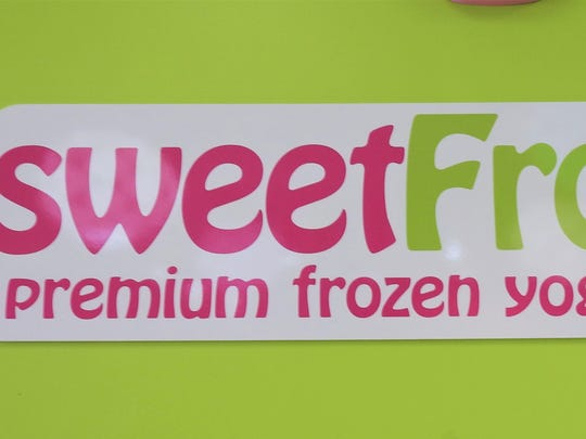 The sweetFrog sign hangs inside the shop. The company's logos are Scoop (left) and Cookie (right).