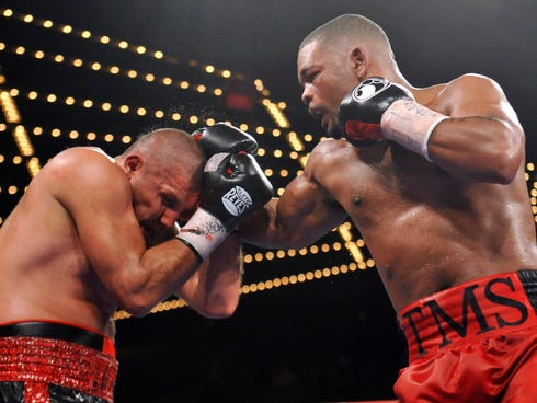 Mike Perez (red trunks) throws a punch that and Magomed Abdusalamov tries to block during their heavyweight fight Saturday.