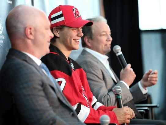 Nico Hischier sits between Devils Head Coach, John