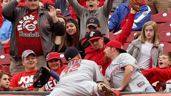 St. Louis Cardinals first baseman Matt Adams (32) dives to the stand after a pop-up off the bat of the Reds' Chris Heisey.