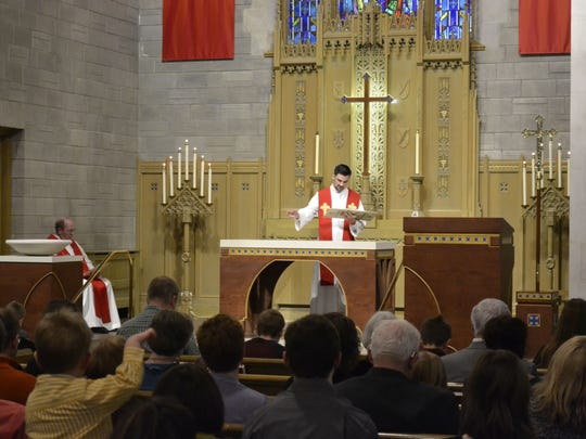 The Rev. Ethan Cherney goes through a Rite of Dedication at the altar during a dedication service Sunday for the renovated St. Paul Lutheran Church in Green Bay. The altar is among several new features in the sanctuary.