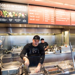 A Chipotle Mexican Grill employee prepares food, in Seattle.
