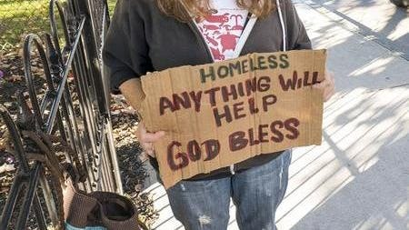 A woman holds a sign in Newport while panhandling in 2016.