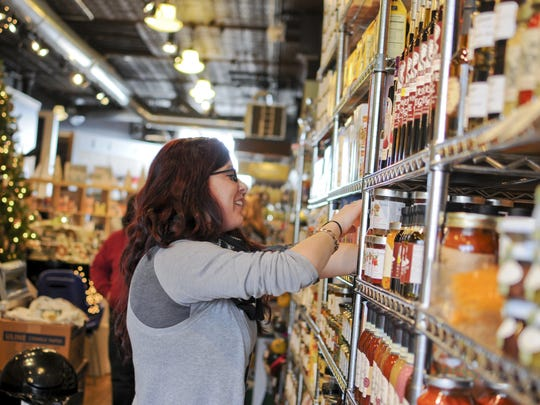 JEFFREY SMITH/TIMES HERALD Employee Brooke Johnston organizes items on a shelf during Small Business Saturday last year at Weekends in downtown Port Huron.
