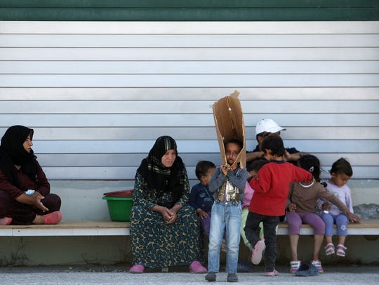Migrants sit inside a new refugees' camp in an abandoned