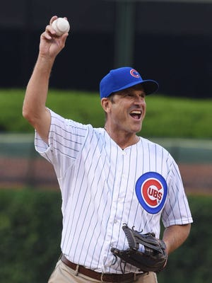 Michigan football coach Jim Harbaugh waves to fans as he takes the mound to throw the first pitch at a baseball game  between the Chicago Cubs and Chicago White Sox on Wednesday, July 27, 2016, in Chicago.