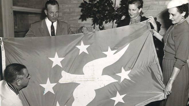 Dan Chamberlain (far left, kneeling) and Jeff Wakefield of the Corpus Christi Chamber of Commerce receive new Corpus Christi flag from Inez Bigler (far right) and Violet Morgan of the Women's Committee of the chamber of commerce in December 1955. The flag was designed by 17-year-old Ray High School student Barbara Hesse in 1952.