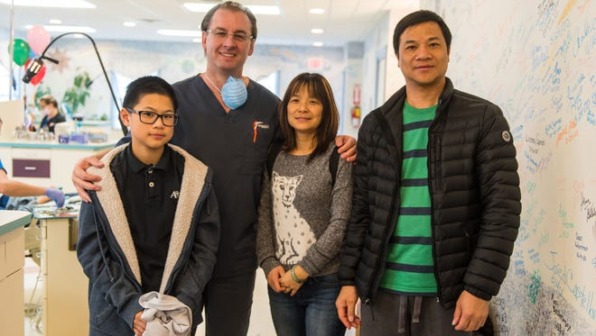 Brian Dong and Dr. James TenBrook pose for a photo with Brian's parents at TenBrook Orthodontics in Vineland on Monday, February 13.