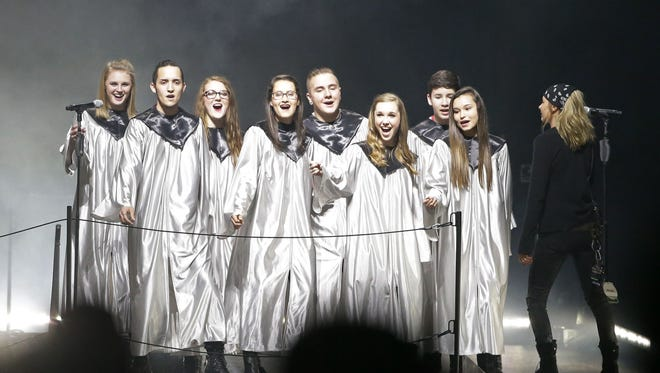 """Choir members from Green Bay East High School perform onstage with Eric Church for the opening number of his sold-out concert Saturday at the Resch Center. Sophomore Kristen Green, third from the right, said, """"It was just an amazing experience."""""""