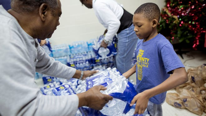 Ezra Tillman III, 6, from Grand Blanc, right, helps Joseph Hampton from Flint, left, move cases of water on Monday, Jan. 11, 2016 at First Trinity Missionary Baptist Church in Flint.