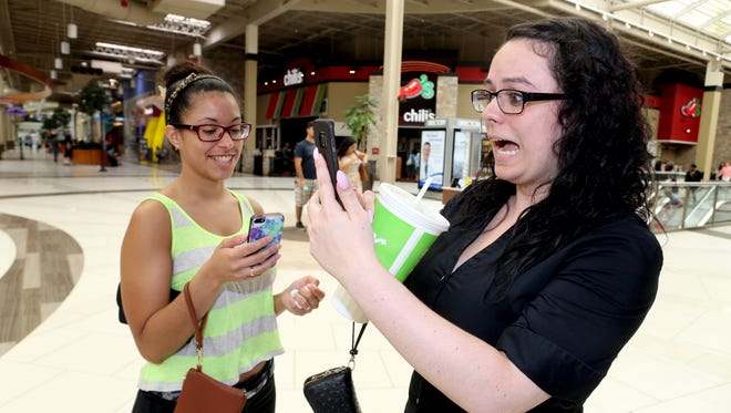 Stephanie Olivieri, 23, and Nina Hernandez, 24, both of Mahopac, spend their afternoon playing Pokemon Go while shopping at the Palisades Center Mall in West Nyack July, 12, 2016.