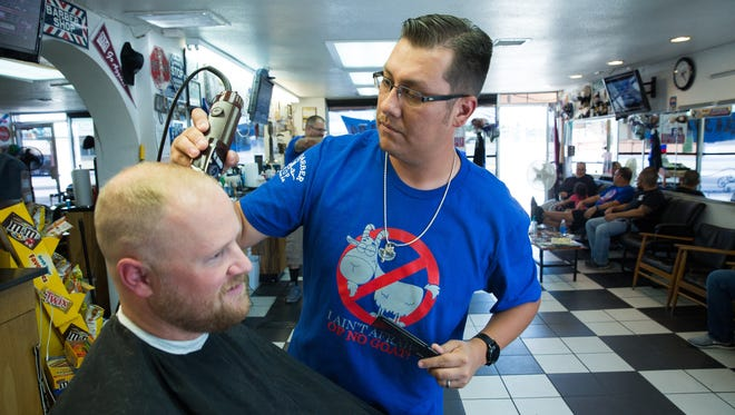 Zach Mirabal, a huge Cubs fan, cuts Andrew Bambrough's hair at the City Barber Shop on N. Main. The barber shop is covered in Cubs memorabilia. The barbers in the shop are ready for the start of the World Series, starting Tuesday night, when the Cubs play the Cleveland Indians. Tuesday October, 25, 2016.
