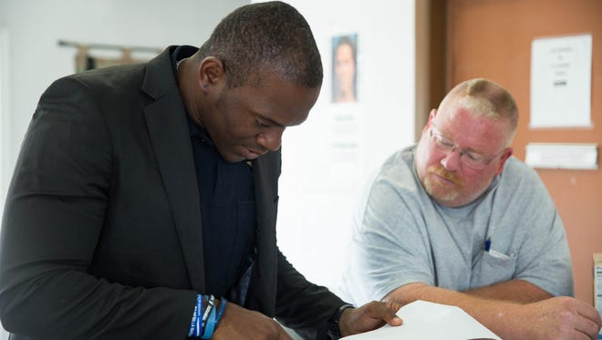 Jamar Cotton, a Doña Ana County sheriff's deputy and one of the 2017 New Mexico True Heroes, talks with Randy Smith, the shelter director at the Gospel Rescue Mission on Tuesday Nov. 21, 2017. Cotton looks over a list of addresses where he will be delivering Thanksgiving dinners to the elderly, veterans or others that might not have access to a good Thanksgiving Day dinner.