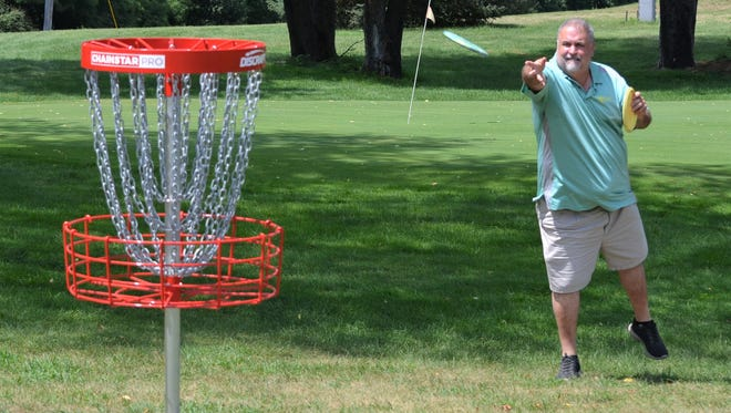 Course designer Jeff Carter makes a throw at the new Springbrook Disc Golf Course, which opened earlier this month.