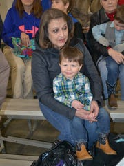 Debi McNutt holds her grandson Connor, 2, who attended The Gala of the Royal Horses equestrian show Wednesday with their family. He and big brother Taylor (back right), 4, wore matching cowboy boots to the show.