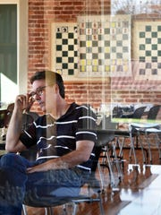 Chess instructor Jeff Bulington sits surrounded by