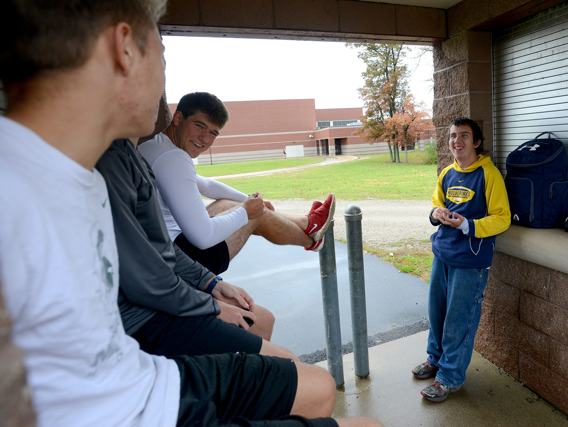 """Ray Latchaw talks and jokes around with teammates before practice for the Laingsburg cross country team Wednesday, October 28, 2015 at Laingsburg High School. Latchaw, a junior, is autistic, but runs, he says, to stay healthy and because he enjoys the """"me time"""" he gets."""
